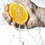 Hand squeezing juice out of an orange