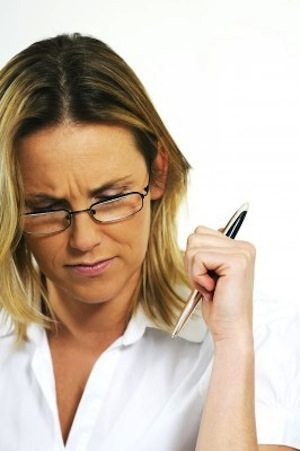 Writer woman with pen looking frustrated